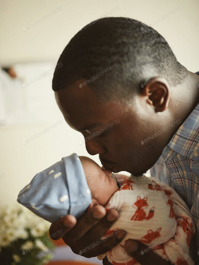 A black father kissing his newborn son on the nose as the sun shines in from the hospital window