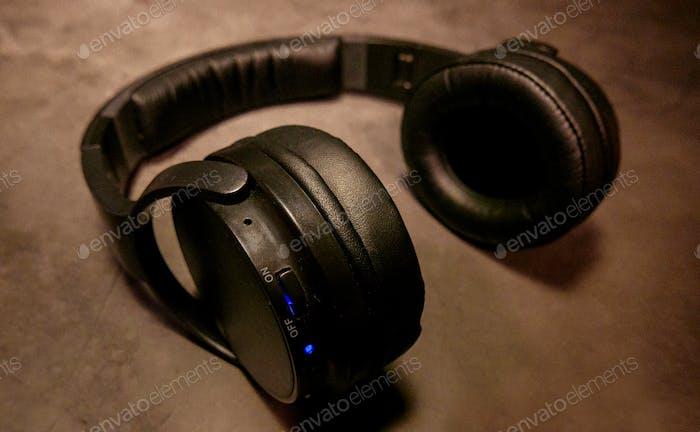 Black wireless bluetooth headphones with a blue light on black backdrop.