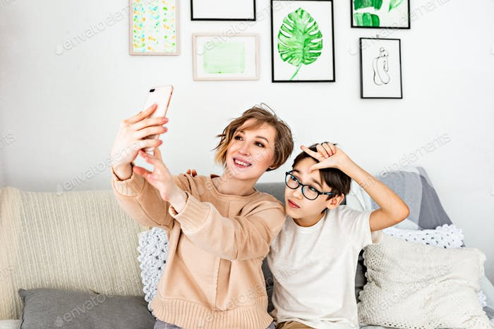 Mom and son teenager taking selfie in cosy living room