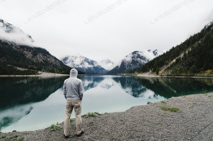 Man looking at an alpine lake at the end of the road.
