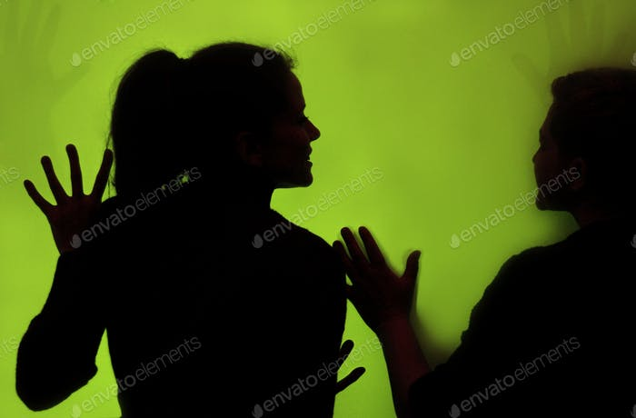 Silhouette of a woman on the green wall background