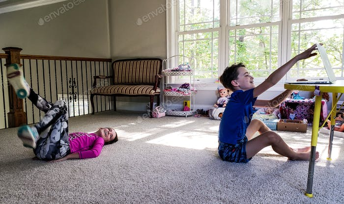 Two kids exercising from home using computer til brother has had enough and shuts it down...