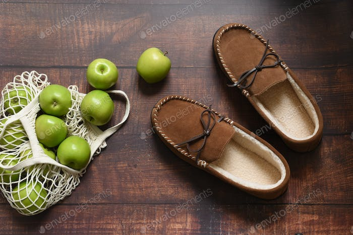 Green apples and slippers on the wooden floor