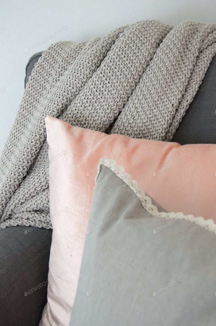 Grey and coral cushions on a chair