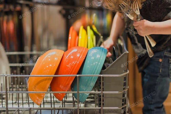 Child loading dish washer