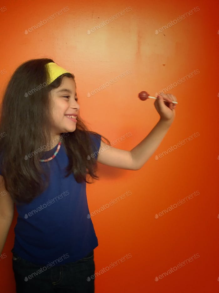 Girl smiling and holding a lollipop against orange wall
