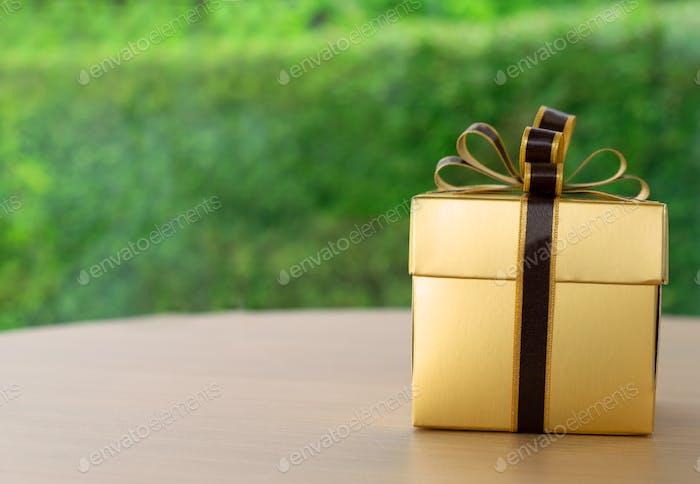 Una caja de regalo envuelta con papel de color dorado y cinta marrón oscuro sobre una mesa con fondo verde