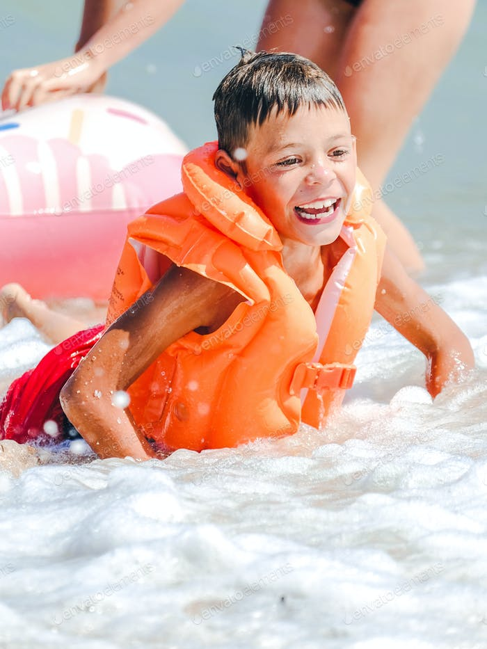 Smiling boy in orange inflatable vest swimming in the sea
