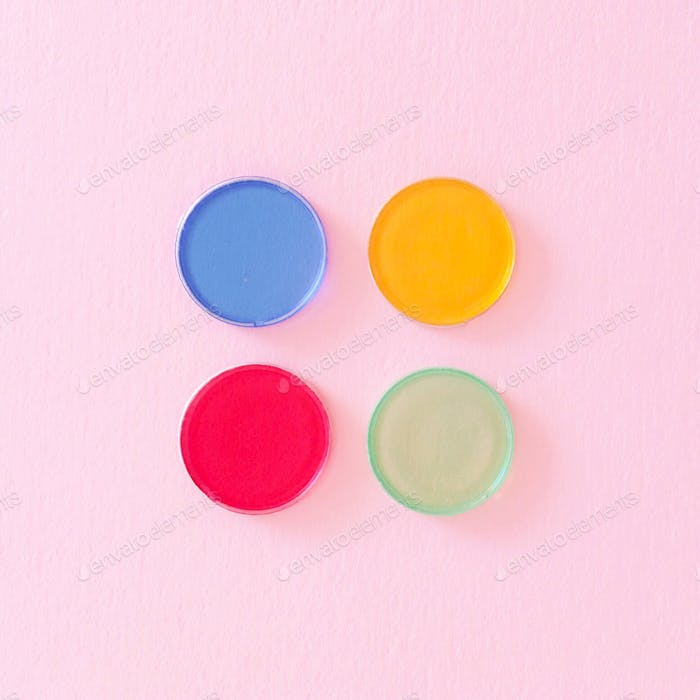 Four primary colored (and green) circular game pieces on a light pastel pink background.