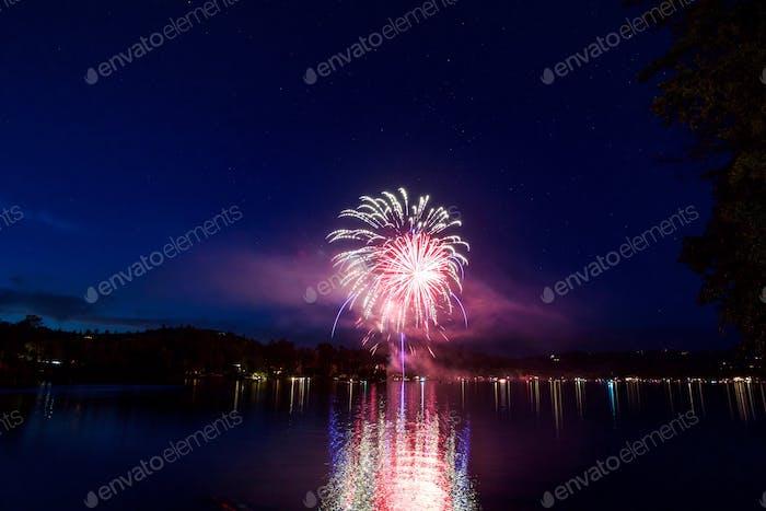 Bunte Feuerwerksexplosion mit roten und blauen Streifen über dem gespiegelten See am marineblauen Nachthimmel