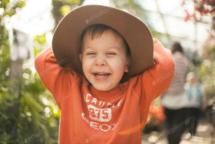 Little toddler boy in hat laughing