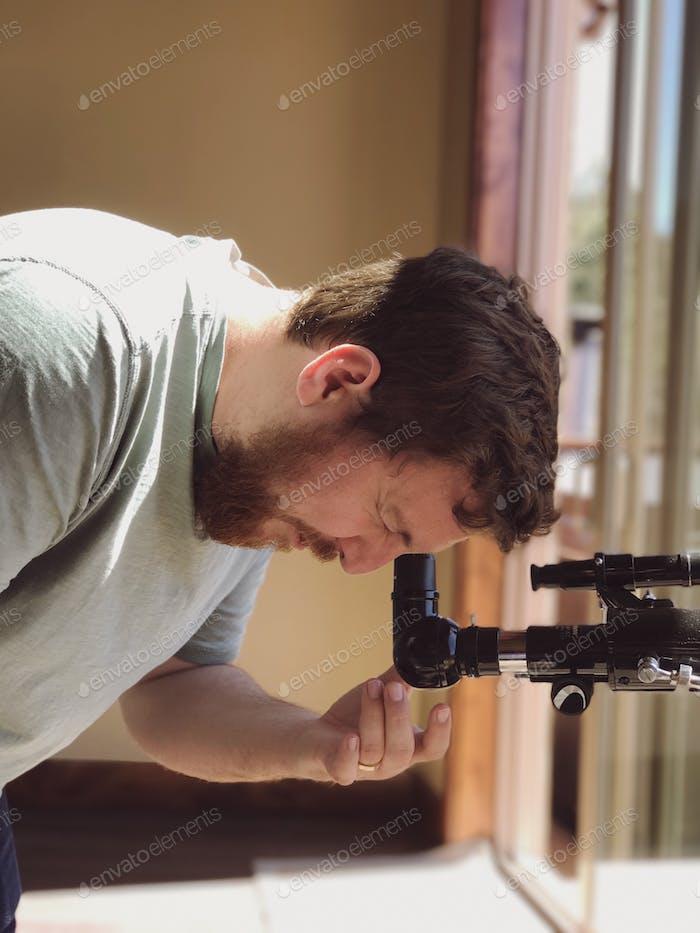 millennial man with beard facial hair looking through telescope at the sky. Solar eclipse astronomy