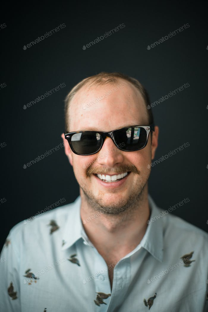 Man, wearing dark sunglasses and a mustache smiles at the camera