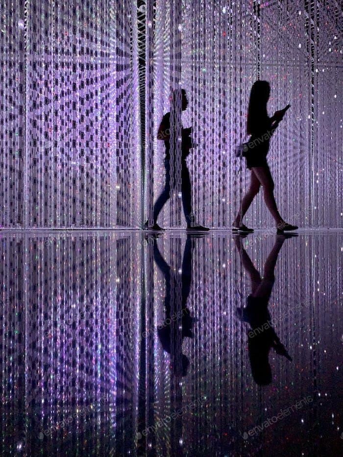 Visitors walking through the Crystal Universe artwork at ArtScience Museum in Singapore.
