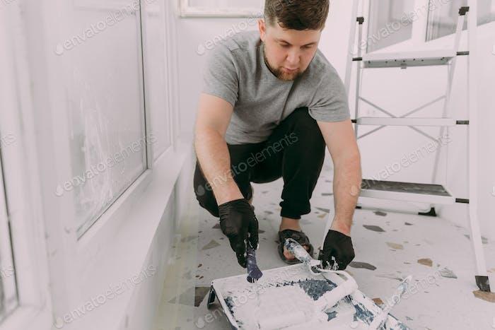 Trabajador manual de treinta años con herramientas de enlucido de paredes dentro de una casa