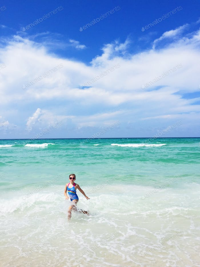 Little girl running, splashing in the Gulf of Mexico.