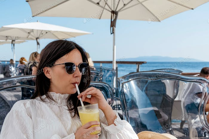 Front view of a young woman sitting and drinking juice on terrace in cafe by sea in Opatija.