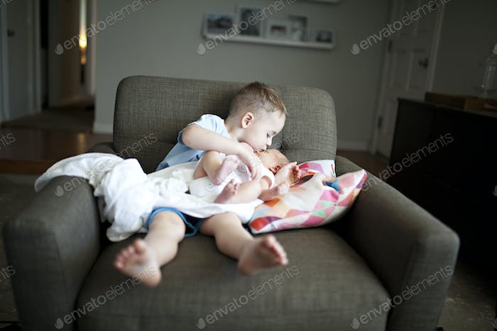 toddler brother holding baby brother
