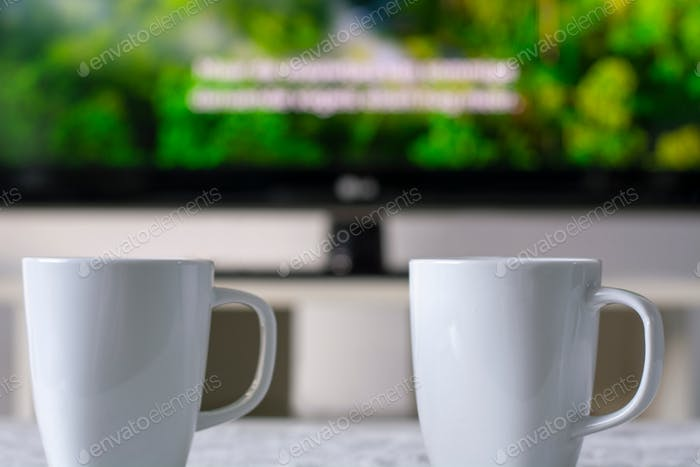 Coffee mugs with a television with a nature documentary and subtitles in background.