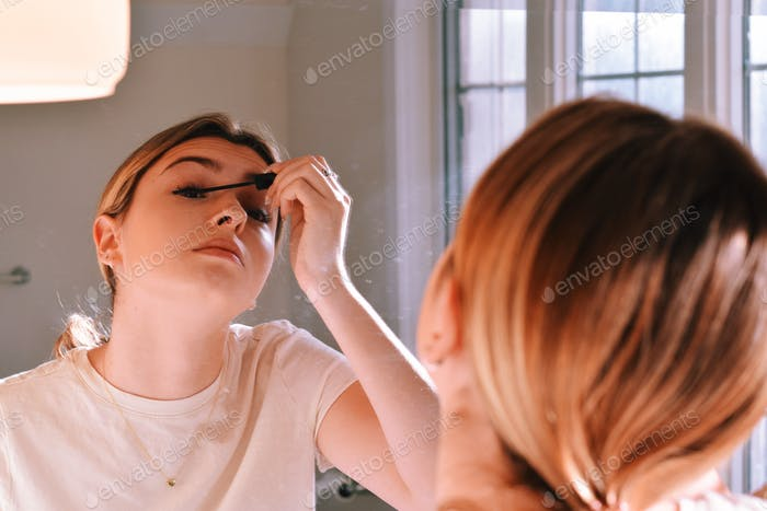 Young teenage girl applying mascara in front of a bathroom mirror, getting ready for the day 💲