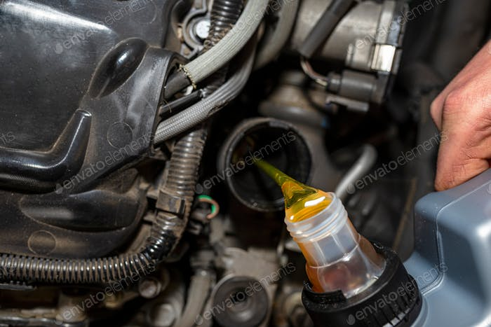 Car mechanic pours new car oil into the engine from a plastic tank in a car workshop