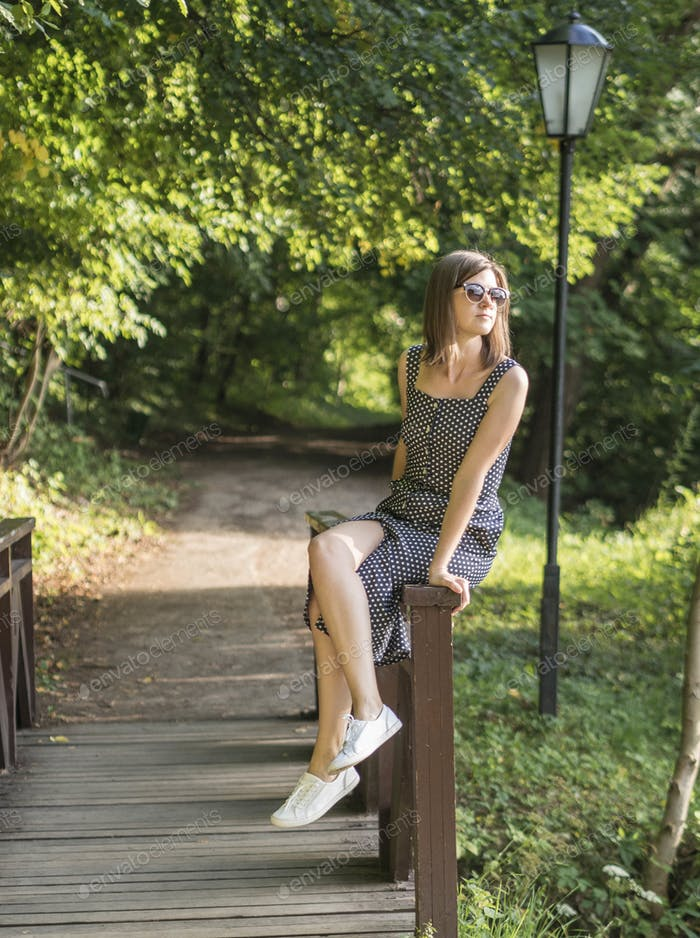 Girl in sundress and sunglasses sits on the railing of a wooden bridge in the park