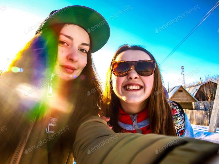 sonnigen wintertag. sonnenflare. mädchen, lächeln. selfie. kalt. winter, beste freunde, schwiegerschwestern