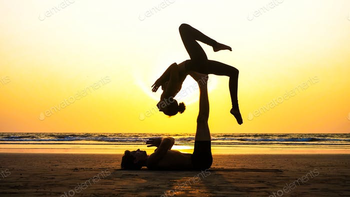 Silhouette of young fit couple practices acrobatic yoga on the beach at sunset