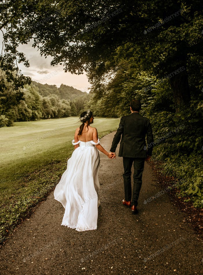 Boho style wedding photo of a young newly wedded couple from behind