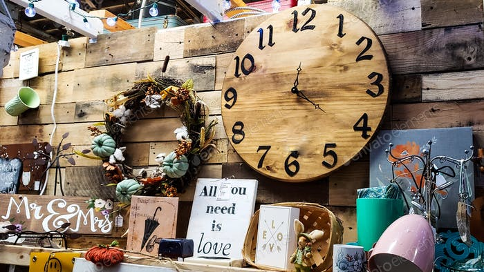 A vintage clock as well as several wild words are present in a store display at an antique store