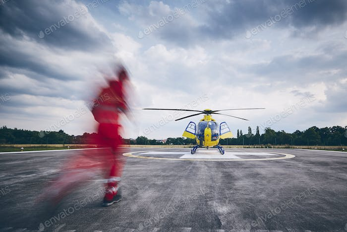 Alarm for helicopter emergency medical service. Paramedic running to helicopter on heliport.