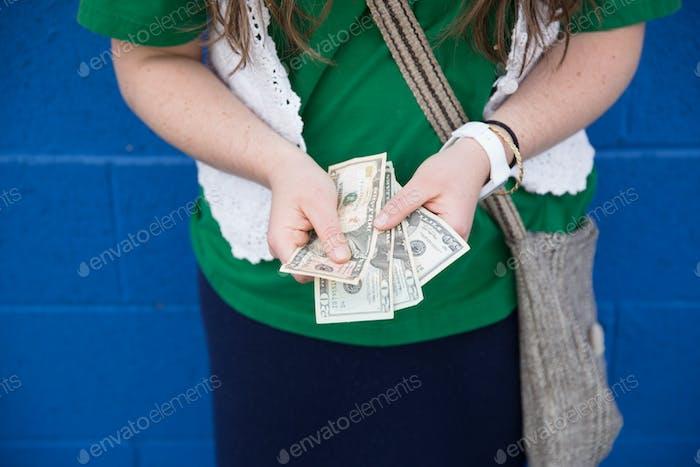 A woman counting several $20 bills