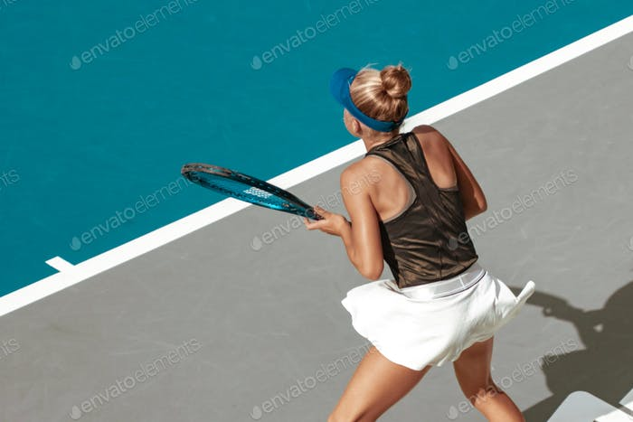 female tennis player, competitive sport, action shot, high angle rear view