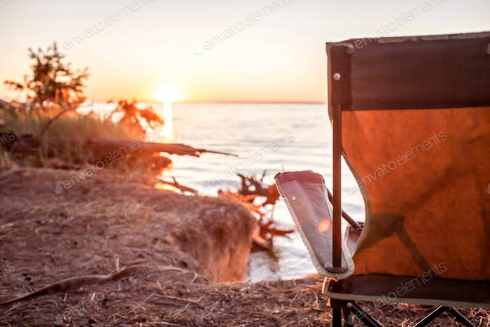 Beautiful sunrise on the wild sea beach at campsite at summer. Local tourism and mental recreation
