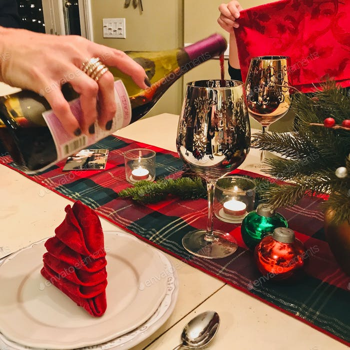 Pouring red wine into a very festive gold wine goblet at the dinner table that is all dressed up for