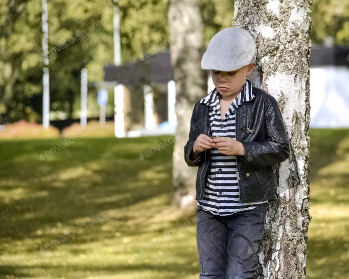 Cute boy leaning against a tree.
