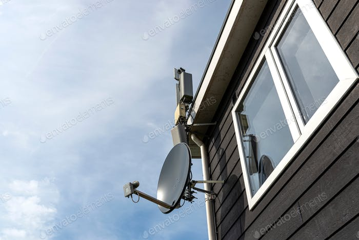 Satellite dish attached to the wooden facade of the house, visible internet and terrestrial TV recei