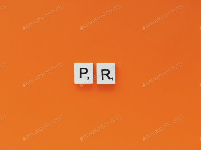 PR, public relations scrabble letters word on a orange background