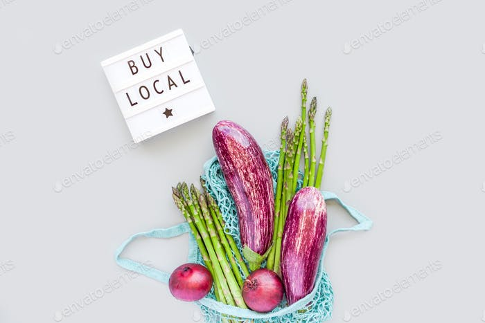 Fresh organic vegetables in eco cotton mesh shopping bag with text Buy Local on lightbox flat lay