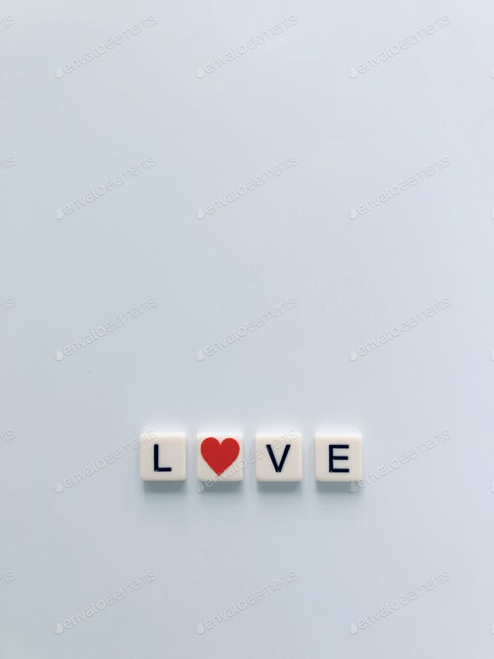 """Flat lay of word LOVE where the """"""""O"""" is replaced with a red heart. Wild words. Minimalism. Red."""