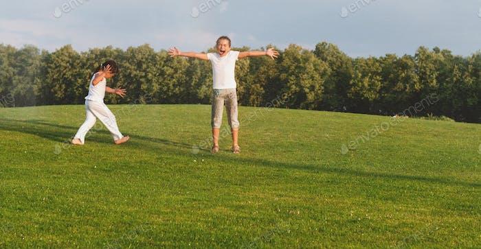 Happy children running under sprinkler water in park
