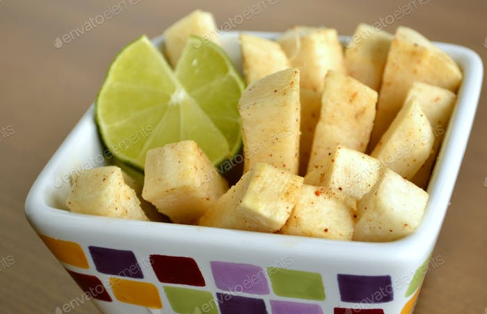 Traditional South American Snack, Jicama slices with lime juice and chili powder.