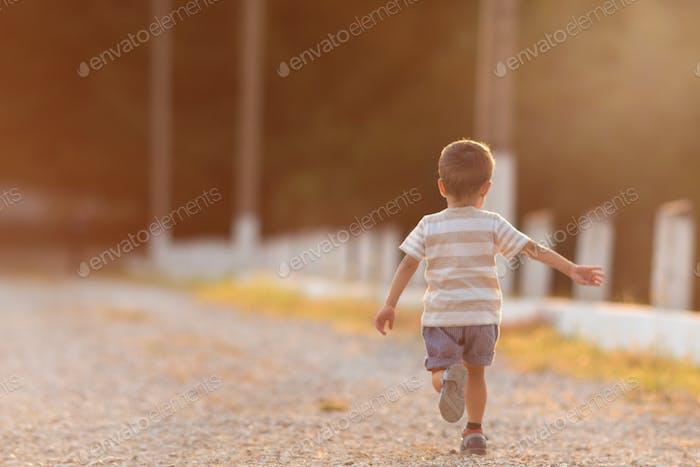 kleiner Junge läuft bei Sonnenuntergang