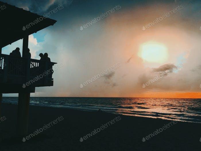 Menschen in Silhouette Am Ozean Pavillon