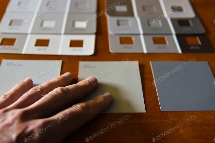 Punto de vista mirando diferentes muestras de pintura en tonos naturales.mano elemento humano. RÍELES