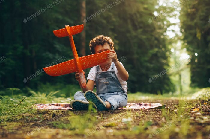 Little boy with curly hair sitting on the ground in the forest with a toy airplane in his hands.
