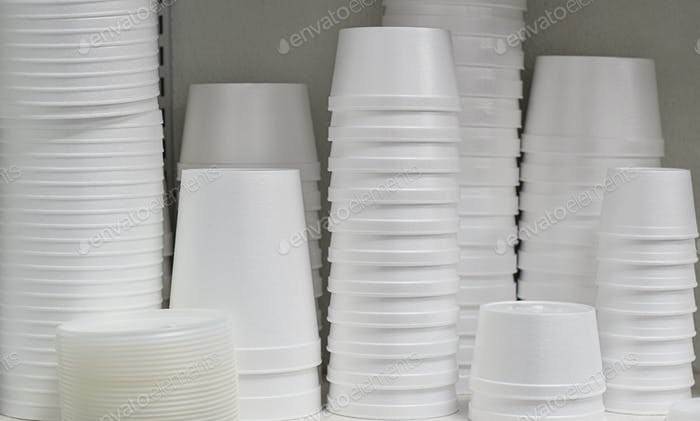 White styrofoam take out disposable containers stacked on a restaurant shelf, environmental issue