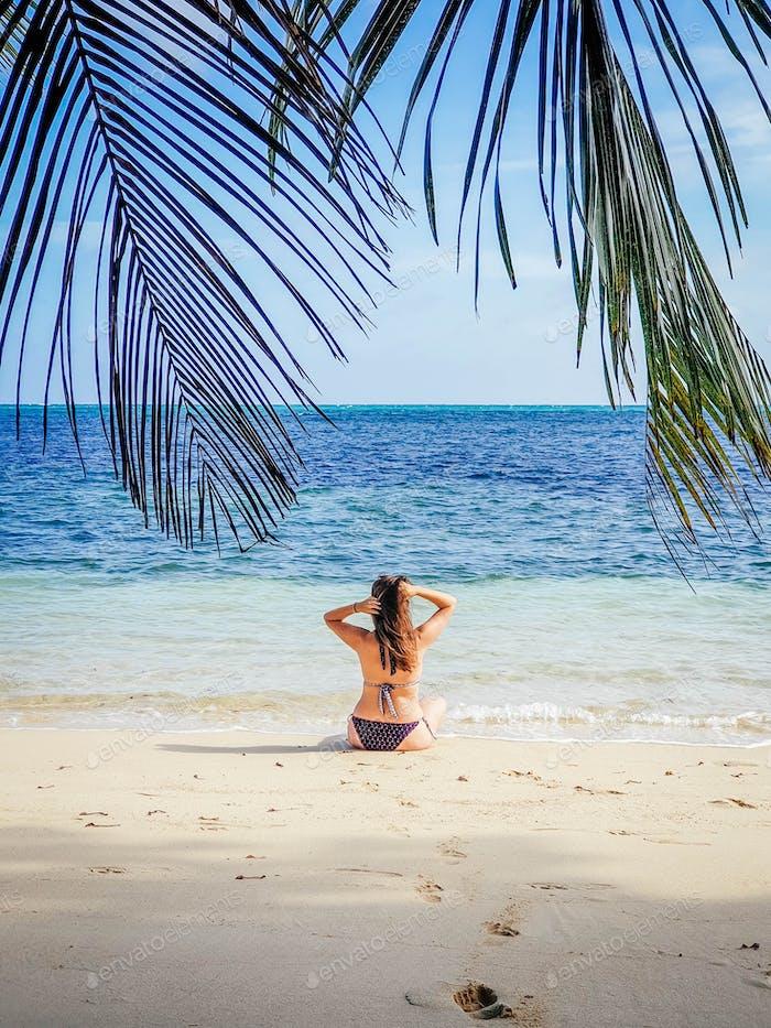 Junge Frau am tropischen Sandstrand. Eine Person, Sommer, Palmen, Sand, Sonne, Himmel, Ozean, Kokosnuss,