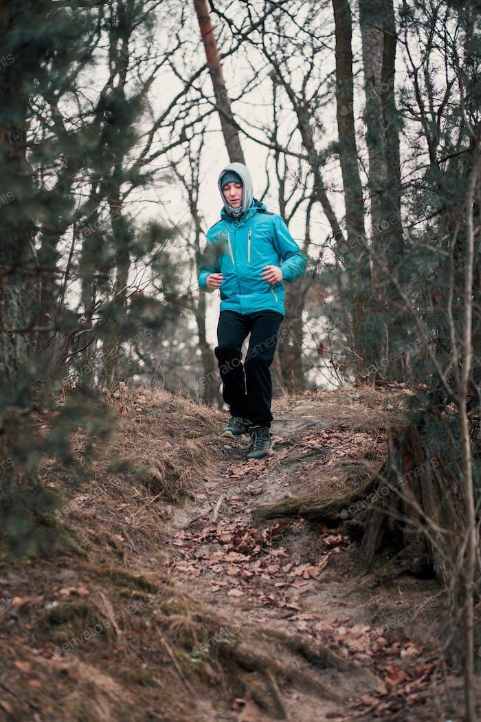 Молодой человек бежит на открытом воздухе во время тренировки в лесу среди безлиственных деревьев в холодный мороз зимний день