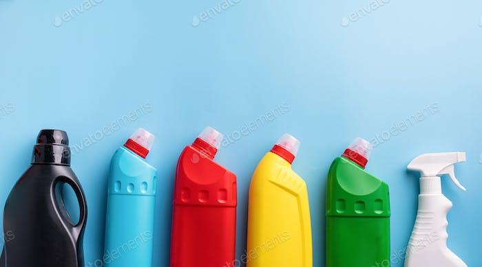 Reinigungsprodukte und Haushaltsführung. Verschiedene Hygieneflaschen flach legen Draufsicht auf blau